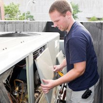 A technician fixing an air-conditioning unit | Heating and Cooling